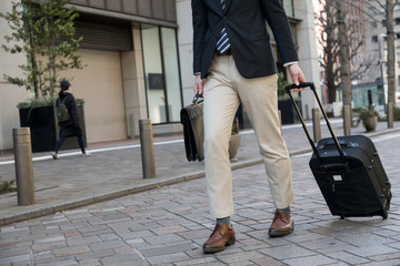 young man carrying a small case with wheels