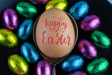 Happy Easter 2017 lettering written on Easter Egg placed on silver spoon with small chocolate eggs in colorful foil for decoration