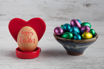 Happy Easter 2017 lettering on egg with red heart shaped holder and chocolate eggs wrapped in foil.