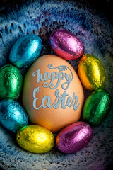 Happy Easter 2017 lettering on egg lined with small chocolate eggs wrapped in colorful foil. Vertical image