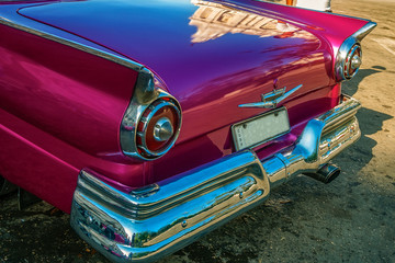 Havana, Cuba -March 14, 2016 - Back detail of a bright colored vintage classic American car in Old Havana, Cuba.