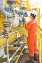 Electrical and instrument technician calibrate gas and condensate flow transmitter Coriolis type by using hand held communicator, Oil and Gas occupational at offshore.