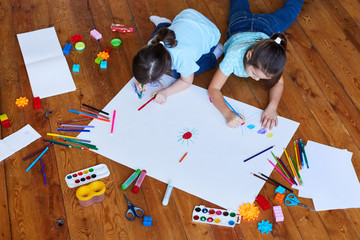 Children draw on a large sheet of paper