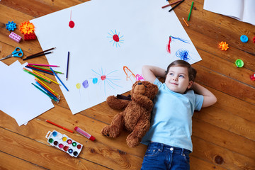 girl lying on the floor with a teddy bear. Girl lying on the floor among the paints and pencils