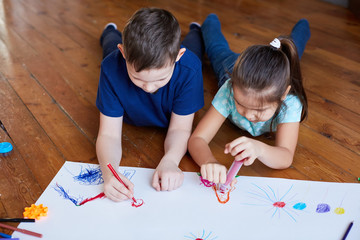 children lying on the floor and drawing. Children draw on a large sheet of paper