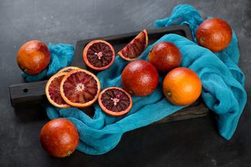 Whole and sliced sicilian blood oranges, studio shot, selective focus