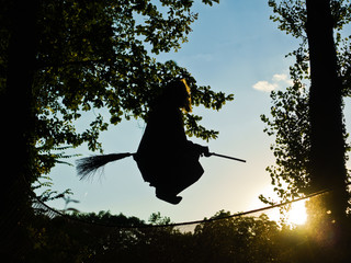 Old witch is flying on a broomstick at sunset