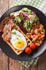 hearty breakfast with fried egg, waffles, bacon, mix salad and beans close-up. Vertical top view