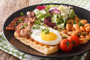 English breakfast with fried egg, waffles, bacon, salad and beans close-up. horizontal
