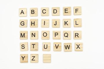 Uppercase alphabet letters on scrabble wooden blocks, isolated on white background