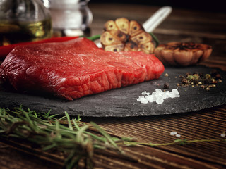 Raw beef steak on a stone plate.