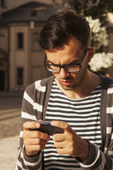 Social Media addiction. young man holding a smartphone (psychological problems, media mania)