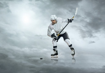 Ice hockey player in action outdoor under sky with clouds