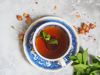 Herbal tea with mint in a blue cup on a saucer on a gray background