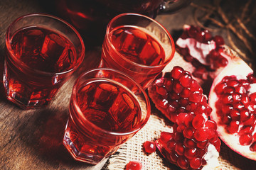 Homemade pomegranate liqueur, still life in rustic style, vintage wooden background, selective focus