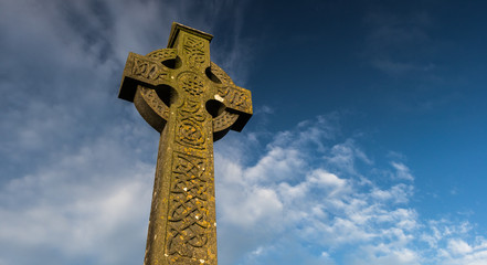 Sunlight hitting celtic cross gravestone at dawn