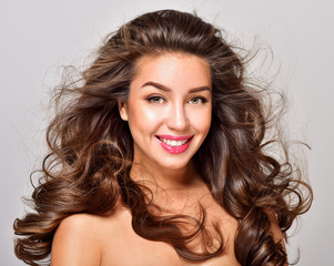 Gorgeous Hair. Beauty Fashion Model Woman with Long and Healthy Brown Hair. Brunette Girl with long curly hair smiling. Professional Makeup.