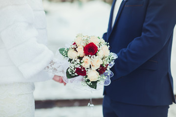 Bride and groom with bouquet to hold gently by the hands at the wedding, close-up in the winter
