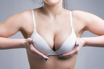 Woman in white push up bra on gray background, perfect female breast
