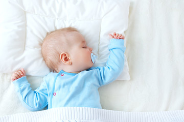 baby sleeping on blue blanket