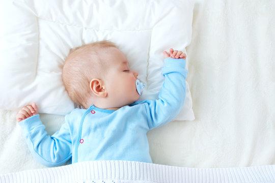 baby sleeping on blue blanket