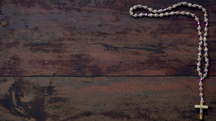 a rosary with beads on wooden textured background. Place for text