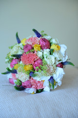 Colorful mixed wedding bouquet positioned on a white cushion