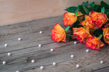 Bouquet of beautiful orange roses on a wooden background and scattered beads of pearls. The best present on birthday.