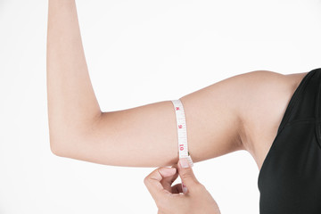 young woman hand holding measuring her thin arm with a tape measure