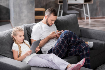 Father and daughter using digital devices
