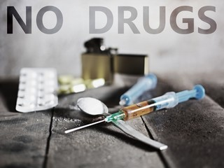 Sign No Drugs. Hard drugs on dark table. A dark theme, drug use.