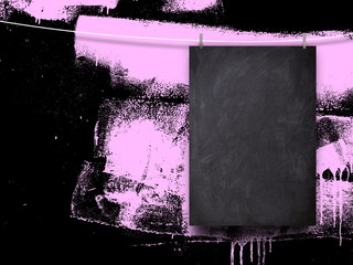 Blank blackboard frame against black and pink splothy abstract background