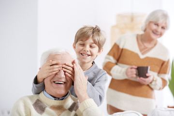 Boy covering his grandfather's eyes