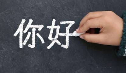 Enfant écrivant Bonjour en chinois à la craie sur une ardoise