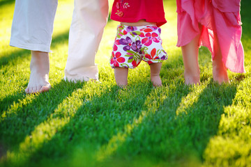 Dad mom and baby - happy family in colorful clothes barefoot on a juicy green lawn