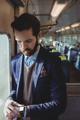 Businessman checking time on smartwatch while travelling