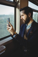 Businessman taking picture from mobile phone while travelling