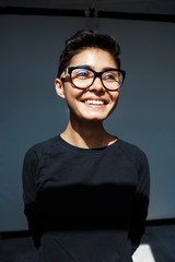 Portrait of young beautiful brunette girl in glasses smiling.