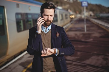 Businessman checking time while talking on mobile phone