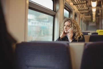 Woman talking on mobile phone inside train compartment