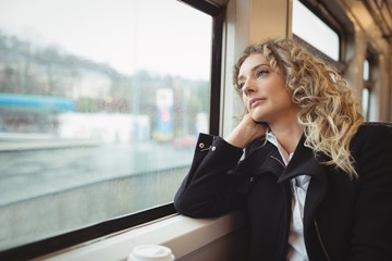 Woman looking out through train window