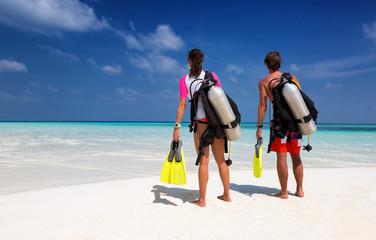 Photo sur Aluminium Plongée Taucher Paar am Strand schaut auf den Ozean
