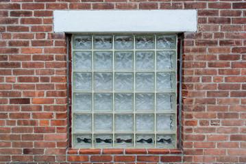 The glass block window on the brick wall