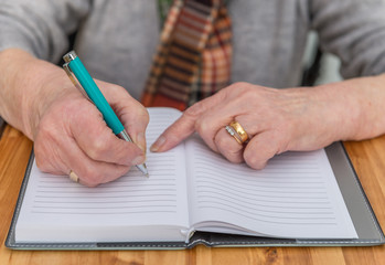 Elderly woman's hands writing in notebook.