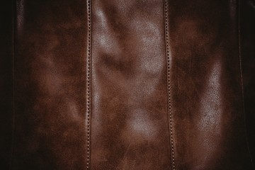 Brown leather texture background surface with seam. Macro shot.