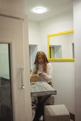 Woman using mobile phone while eating salad