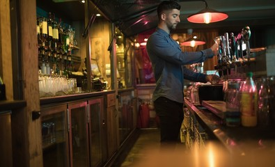 Bartender filling beer from bar pump