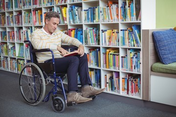 Attentive disabled school teacher reading book in library