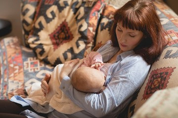 Mother breast feeding her baby on sofa