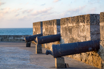 Cannons lined up in the sunset with the Caribbean sea in the background in Cartagena, Colombia.